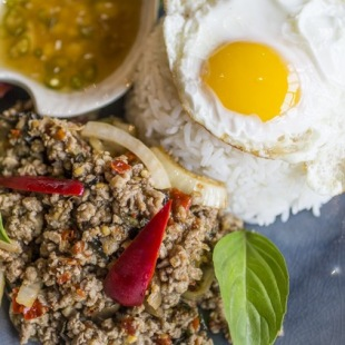 Holy basil and a fried egg sit atop a dish of spicy ground pork at Thai Kun. Ricardo B. Brazziell/AMERICAN-STATESMAN