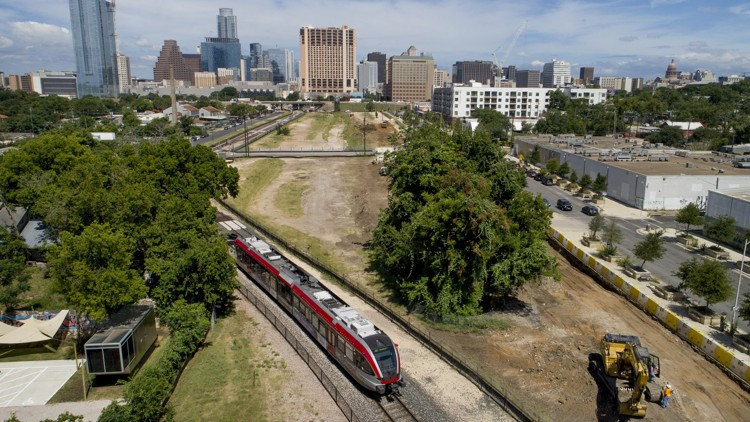 A MetroRail train runs along the Plaza Saltillo site in East Austin on Thursday as construction begins on a mixed-use development on the Capital Metro-owned land. JAY JANNER / AMERICAN-STATESMAN